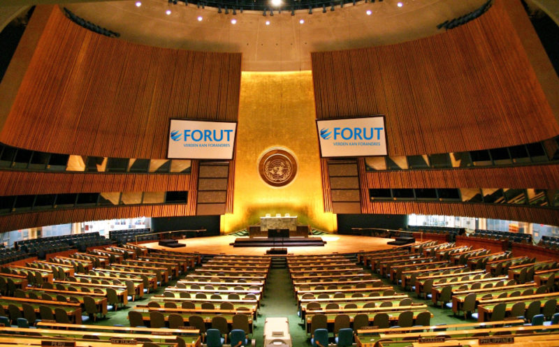 FNs plenumssal med FORUT-logo